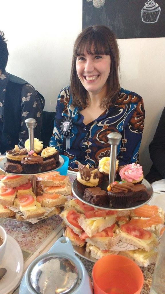 Claire sitting in front of afternoon tea with lots of cakes